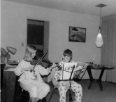 This is from Christmas 1964, when my parents thought it would be great for my brother & myself to play Christmas songs. I am on the violin, and my brother is on the clarinet. Each of our sheet music was apparently in a different key. You can guess how it sounded ;-) but it made our parents happy. Neither of us continued to play music more than a few more years, but it did give us an appreciation of the effort involved to play good music, let alone great music. - Carol